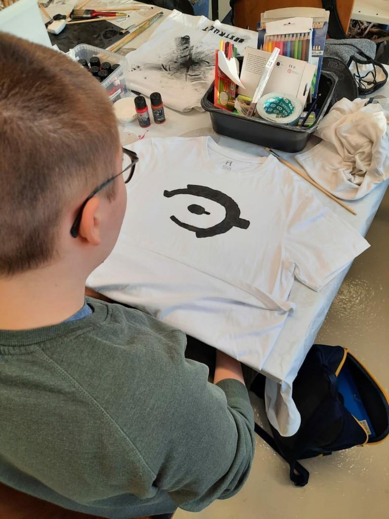 Opiskelija painaa paitaa taidestudiolla