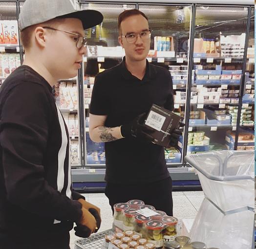 Kaksi opiskelij hyllyttää tavaraa kaupassa.