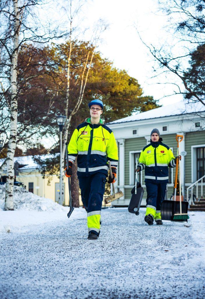 Kaksi kiinteisönhuollon opiskelijaa kävelee lumisella pihalla.