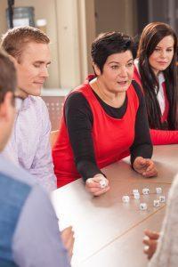 Neljä ihmistä pöydän ääressä edessään kuvanoppia