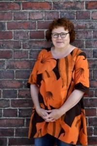 kuvassa Sirpa Tampereen kv-vsataava hymyillen oranssissa mekossa