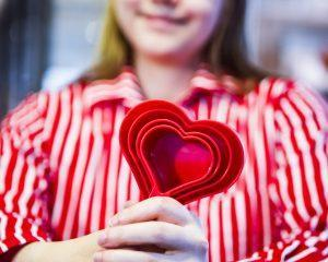 Opiskelija pitää käsissään sydämen muotoista muottia.
