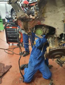 Kaksi nuorta työhaalareissaan ovat irrottamassa jarrukenkien vanhasta autosta. Ympärillä näkyy työkaluja.