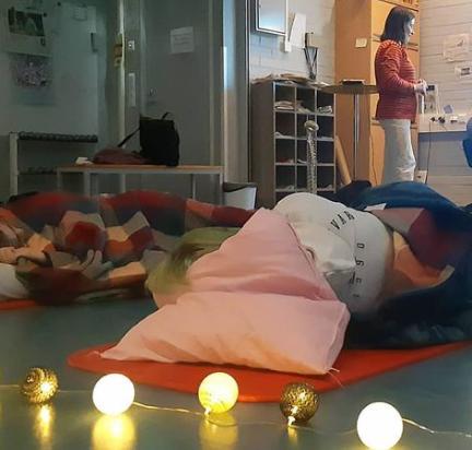 Opiskelijat rentoutumassa lattialla maaten