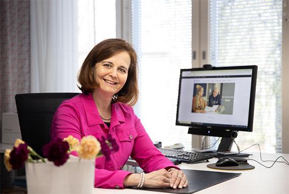 Tiina Immonen kuvattuna työpöydän äärellä.