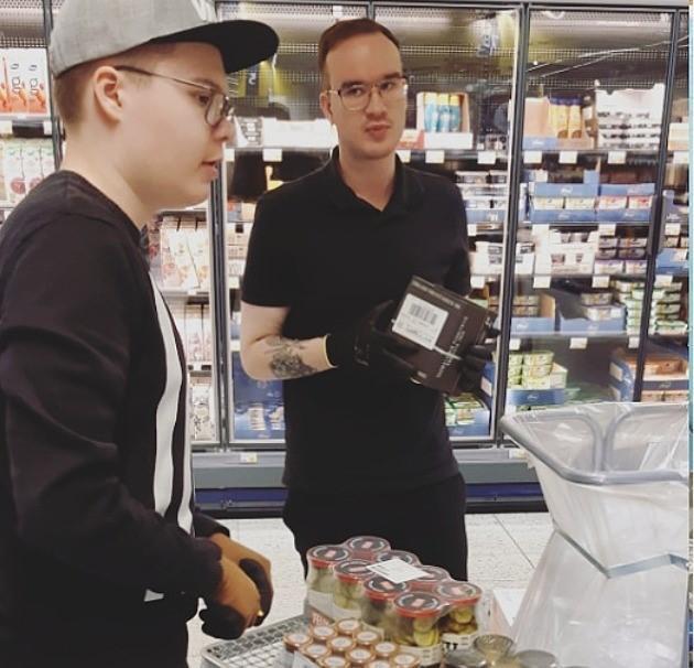 Kaksi opiskelijaa työtehtävissä kaupassa.