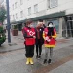Kolme henkilöä seisoo kadulla nälkäpäiväkeräyksen liivit päällään ja keräyslippaat kädessään, kasvoillaan kasvomaskit.