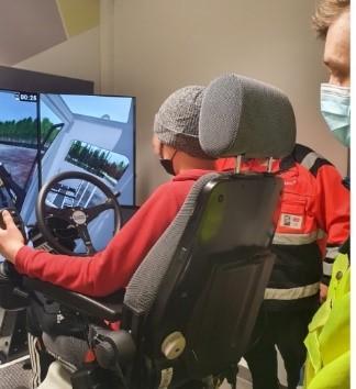 Opiskelija ajaa simulaatioajoneuvoa, kuva takaa päin
